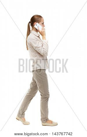 side view of a woman walking with a mobile phone. back view ofgirl in motion.  backside view of person.  Rear view people collection. Isolated over white background. Skinny girl in white denim suit