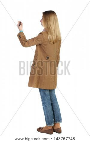 back view of writing beautiful woman. Rear view people collection.  backside view of person. Isolated over white background. The blonde in a brown coat paints a felt-tip pen plan