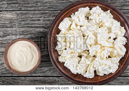 organic cottage cheese on a clay plate sour cream in a small bowl on the old wooden table top view