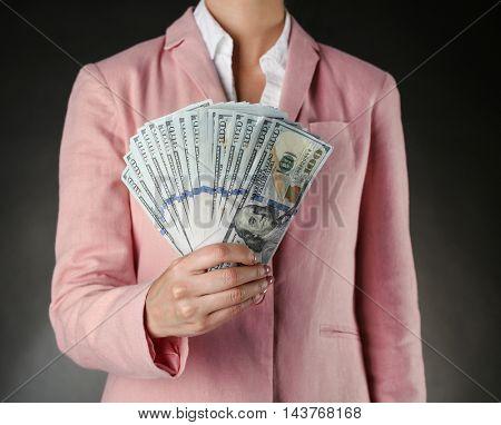 Woman with money on dark background