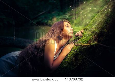 Beautiful girl with long hair in a mystical forest.