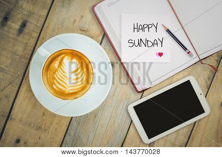 Happy Sunday on paper with coffee cup on wood background