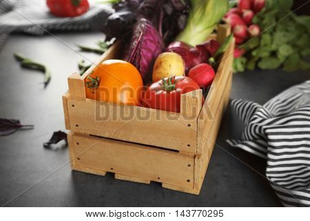Fresh vegetables in wooden box on table