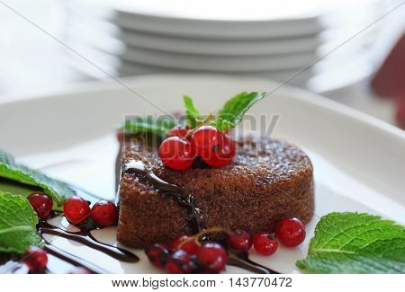 Delicious fondant with red currant on plate, closeup