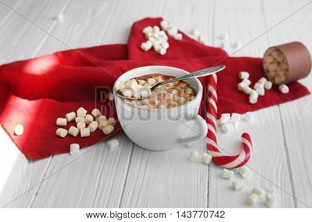 Cup of hot chocolate with marshmallows and candy on table