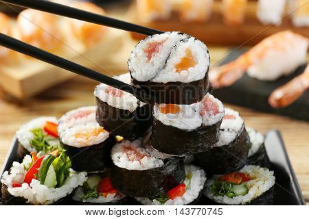 Tasty sushi roll with black chopsticks, closeup