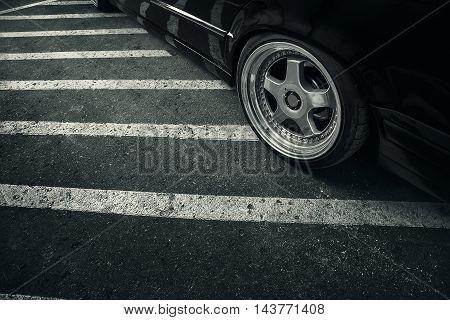 Modern rims on wheel of black car at asphalt road