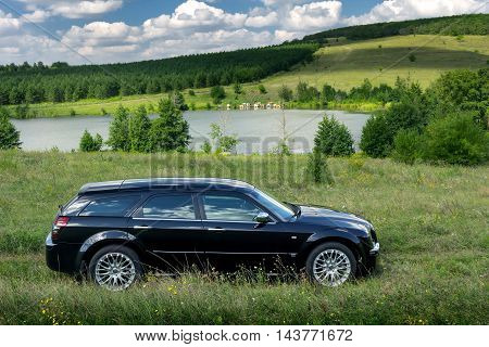 Saratov, Russia - August 9, 2015: Black car Chrysler 300c stand off-road near lake at daytime