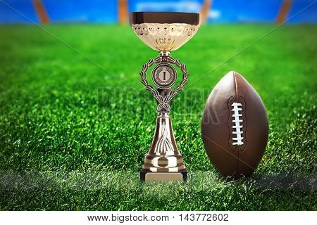 American football and trophy cup on green field