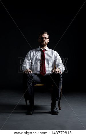 Businessman sitting in armchair over black background. Business and office concept.