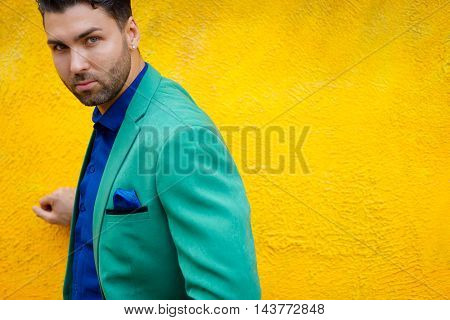 Fashionable brunette guy posing on background of yellow wall