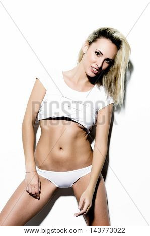 Beautiful  slim girl with blond straight hair is posing in the white studio