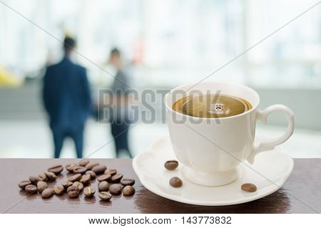 Hot coffee on table with blur background of work office
