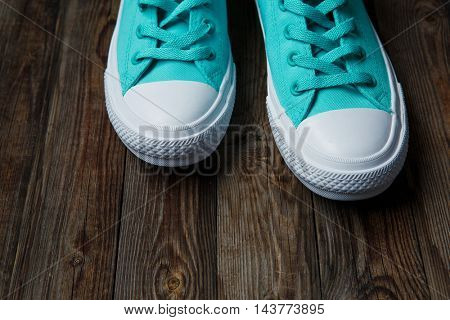 blue shoes over empty wooden floor