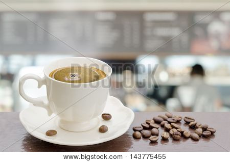 Hot coffee cup on table with blur background of coffee shop