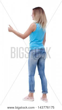 Back view of  woman thumbs up. Rear view people collection. backside view of person. Isolated over white background. The blonde in a blue shirt and jeans showing thumbs up.