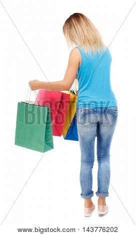 back view of woman with shopping bags. backside view of person.  Rear view people collection. Isolated over white background. The blonde in a blue shirt and jeans looks into colored packets.