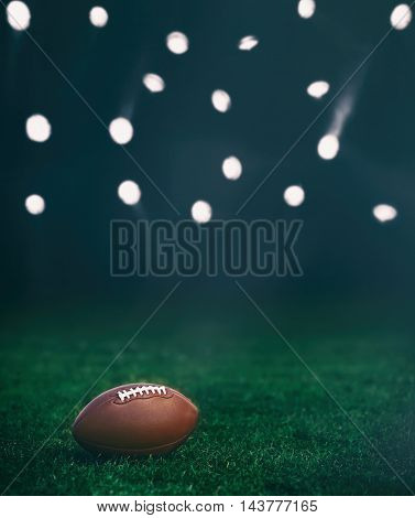 American football ball on a green grass on dark background and spotlight with laser rays