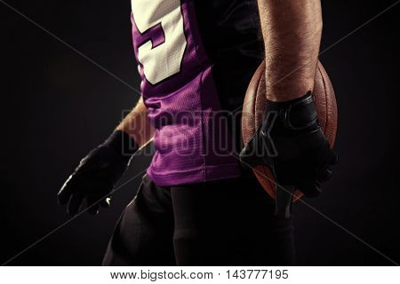 Hands of american football player holding ball on black background