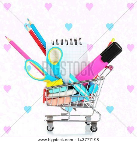 Shopping cart with colorful stationery and notebook on color background. School concept.