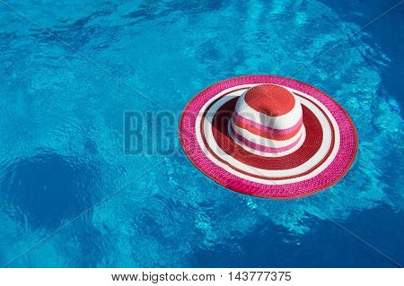 Pink summer hat floating on water in swimming pool