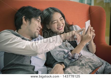 asian younger man and woman watching on smart phone with happy faceinternet and social media connecting concept