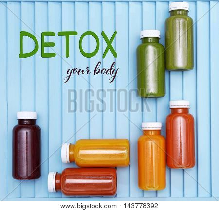 Bottles with delicious detox drinks and text detox your body on blue wooden background. Detox diet concept.