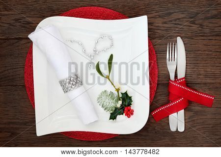 Christmas dinner table setting with white square porcelain plate, napkin, silver bead strand, holly, mistletoe and cutlery with red ribbon over oak wood background.