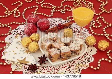 Christmas still life with egg nog, stollen cake bites on a heart shaped plate, gold foil wrapped chocolates, spices and gold bead decorations on a red background.
