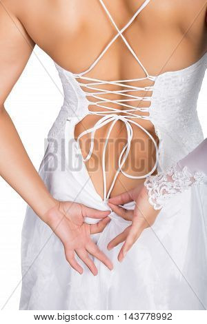 Bride putting on her white wedding dress, closeup hands and lace dress. young woman tying up her wedding dress.