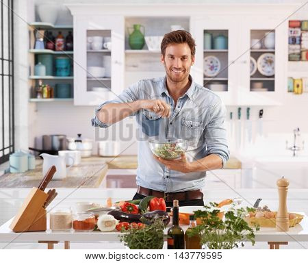 Handsome young man preparing salad at home in kitchen, smiling happy, looking at camera.