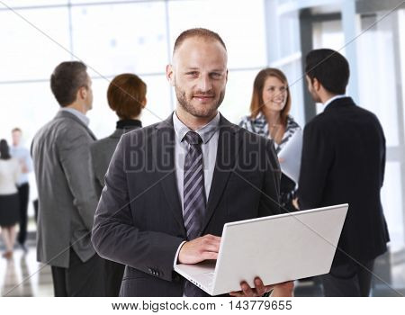Corporate caucasian businessman with laptop at office, smiling.
