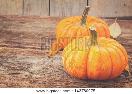 orange pumpkins with fall leaves on wooden textured table, retro toned