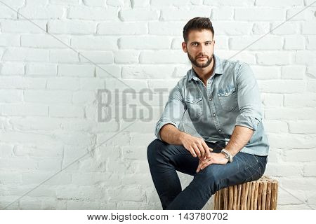 Young goodlooking caucasian man sitting at white brick wall, plenty of copyspace.