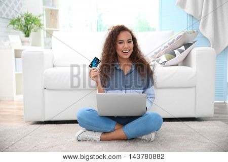 Beautiful young woman using credit card and laptop for online shopping