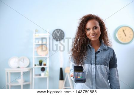Beautiful young woman holding bank terminal in shop