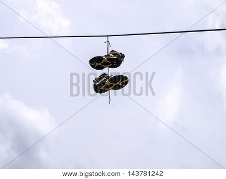 Old pair of tennis shoes hanging from the middle of power lines
