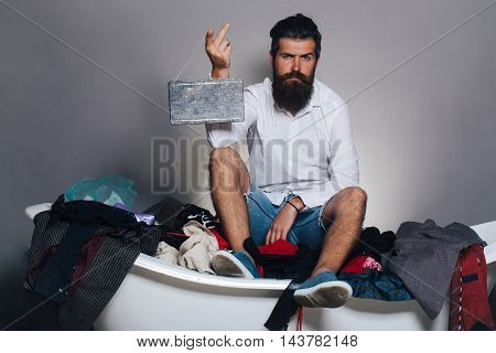 young handsome bearded man with long beard and stylish haircut on bathtub with many colorful clothes holding small wooden board on grey background copy space
