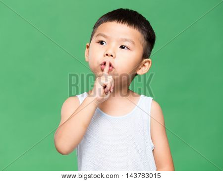 Little boy putting a finger on lips