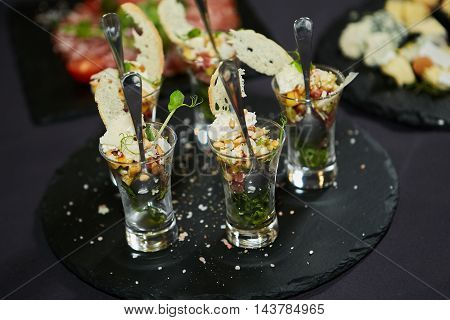 Beautifully decorated catering banquet table with different food snacks and appetizers with sandwich caviar fresh fruits on corporate christmas birthday party event or wedding celebration