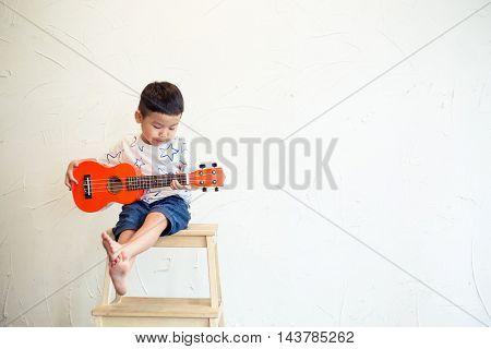 Asian boy playing ukulele