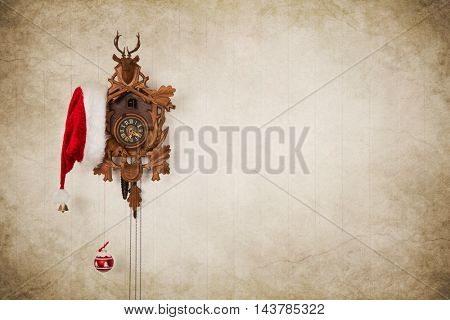 Old cuckoo clock with santa hat for christmas decoration on old wooden vintage background.