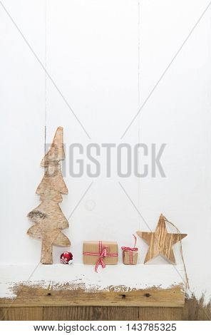 Christmas gift boxes with carved tree and star on white wooden shabby background for decoration items.