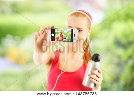 Young woman making selfie photo with sports bottle on blurred nature background