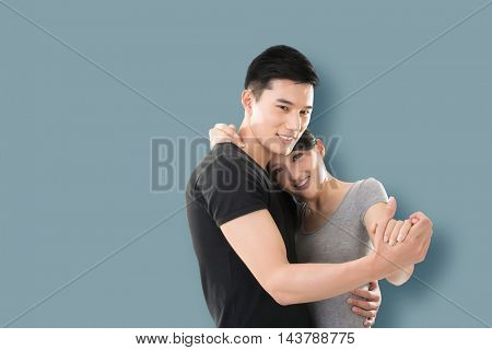 young Asian couple dancing with smiling face against colorful background