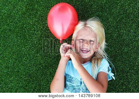 beautiful blonde smiling girl lying on the grass and holding a red ball