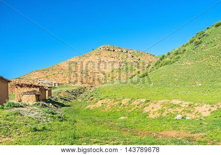 The red mountain and small earthen houses in Zarmas village Uzbekistan.