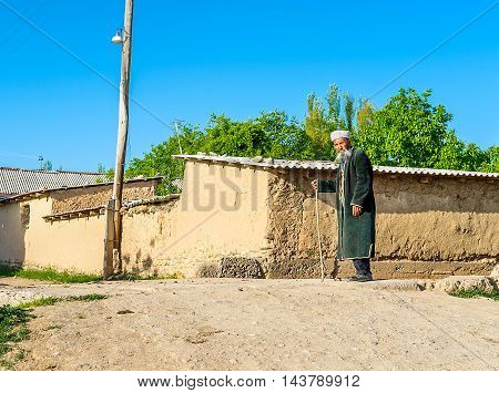 SAMAK UZBEKISTAN - MAY 2 2015: The senior man in traditional costume and with the walking stick walks along the street of kishlak (village) with the earthen houses on the background on May 2 in Samak.