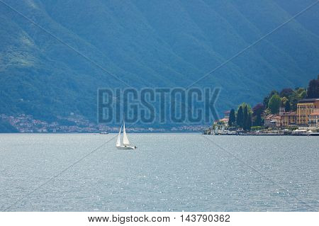 Yacht at lake Como on the background of Varenna town summer time