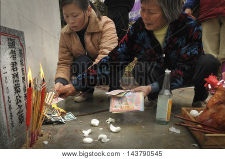 TAISHAN, CANTON, CHINA - 28 Jan 2008: A traditional Chinese memorial ceremony taking place at a rural grave site.